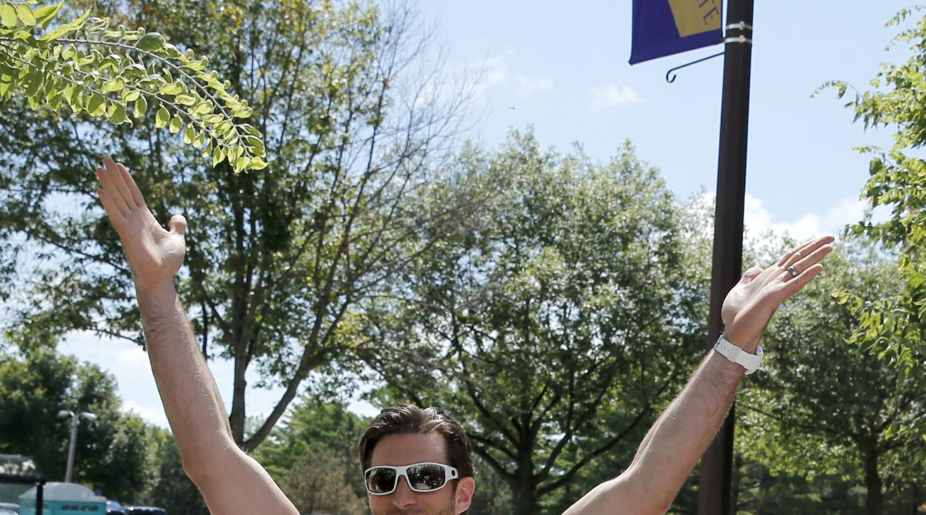 Minnesota Vikings defensive end Brian Robison, raises his hands to the cheers of fans as he reports to an NFL football training camp on the campus of Minnesota State University Saturday, July 25, 2015, in Mankato, Minn. (AP Photo/Charles Rex Arbogast)