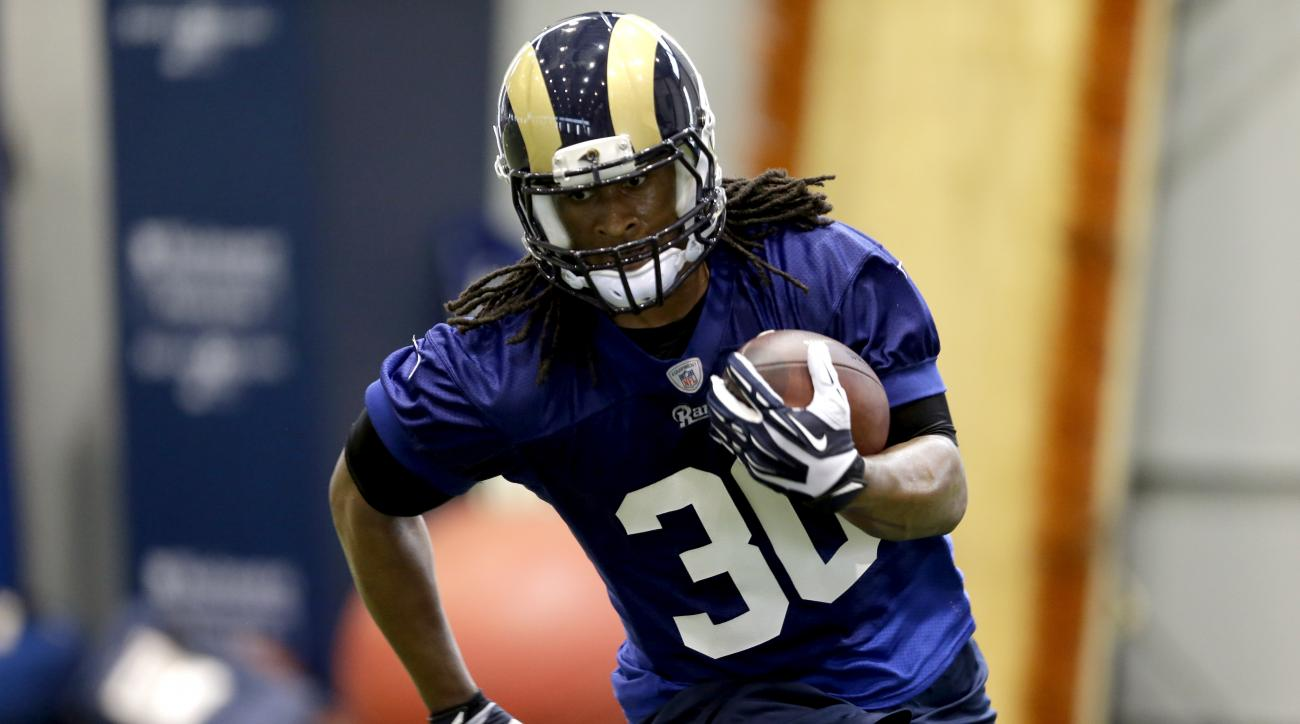 FILE - In this June 4, 2015, file photo, St. Louis Rams running back Todd Gurley runs with the ball during an NFL football organized team activity in St. Louis. The former Georgia standout was the 10th pick of the draft even though he was coming off midse