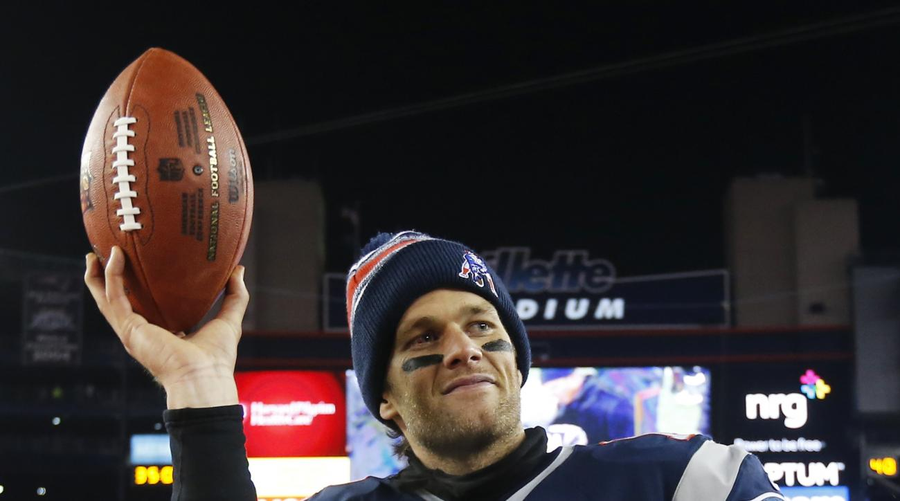 FILE - In this Jan. 10, 2015, file photo,New England Patriots quarterback Tom Brady holds up the game ball after an NFL divisional playoff football game against the Baltimore Ravens in Foxborough, Mass. Brady's four-game suspension for his role in using u