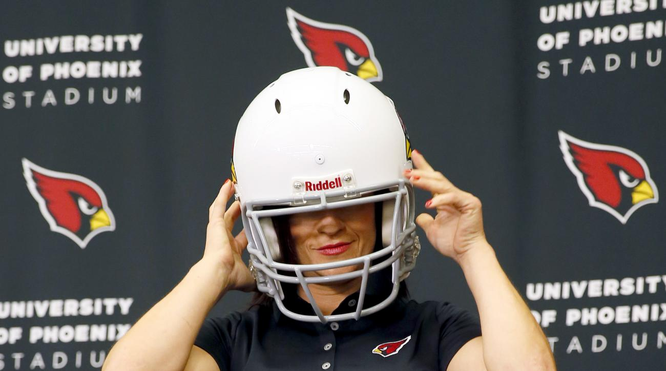 Arizona Cardinals training camp coach Dr. Jen Welter poses for photographers after being introduced, Tuesday, July 28, 2015, at the teams' training facility in Tempe, Ariz. Welter is believed to be the first female to hold a coaching position of any kind