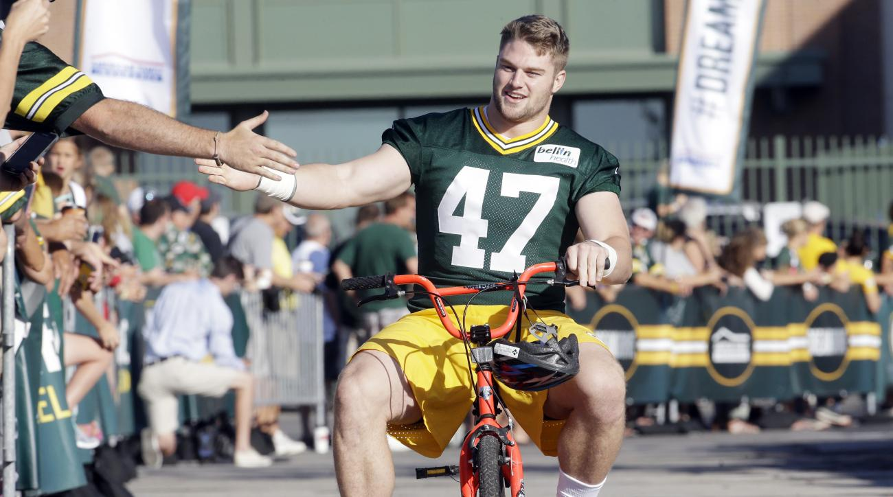 Green Bay Packers' Jake Ryan rides a bike to NFL football training camp Thursday, July 30, 2015, in Green Bay, Wis. (AP Photo/Morry Gash)