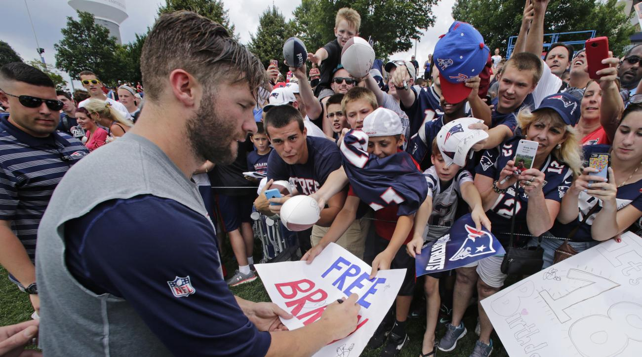 "New England Patriots wide receiver Julian Edelman signs an autograph for a fan on a ""Free Brady"" sign during an NFL football training camp in Foxborough, Mass., Thursday, July 30, 2015. (AP Photo/Charles Krupa)"