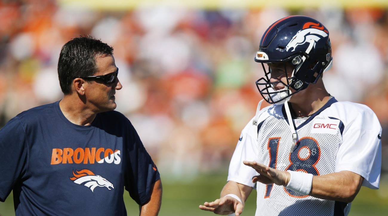 Denver Broncos quarterback Peyton Manning, right, confers with quarterbacks coach Greg Knapp at the team's NFL football training camp Friday, July 31, 2015, in Englewood, Colo. (AP Photo/David Zalubowski)