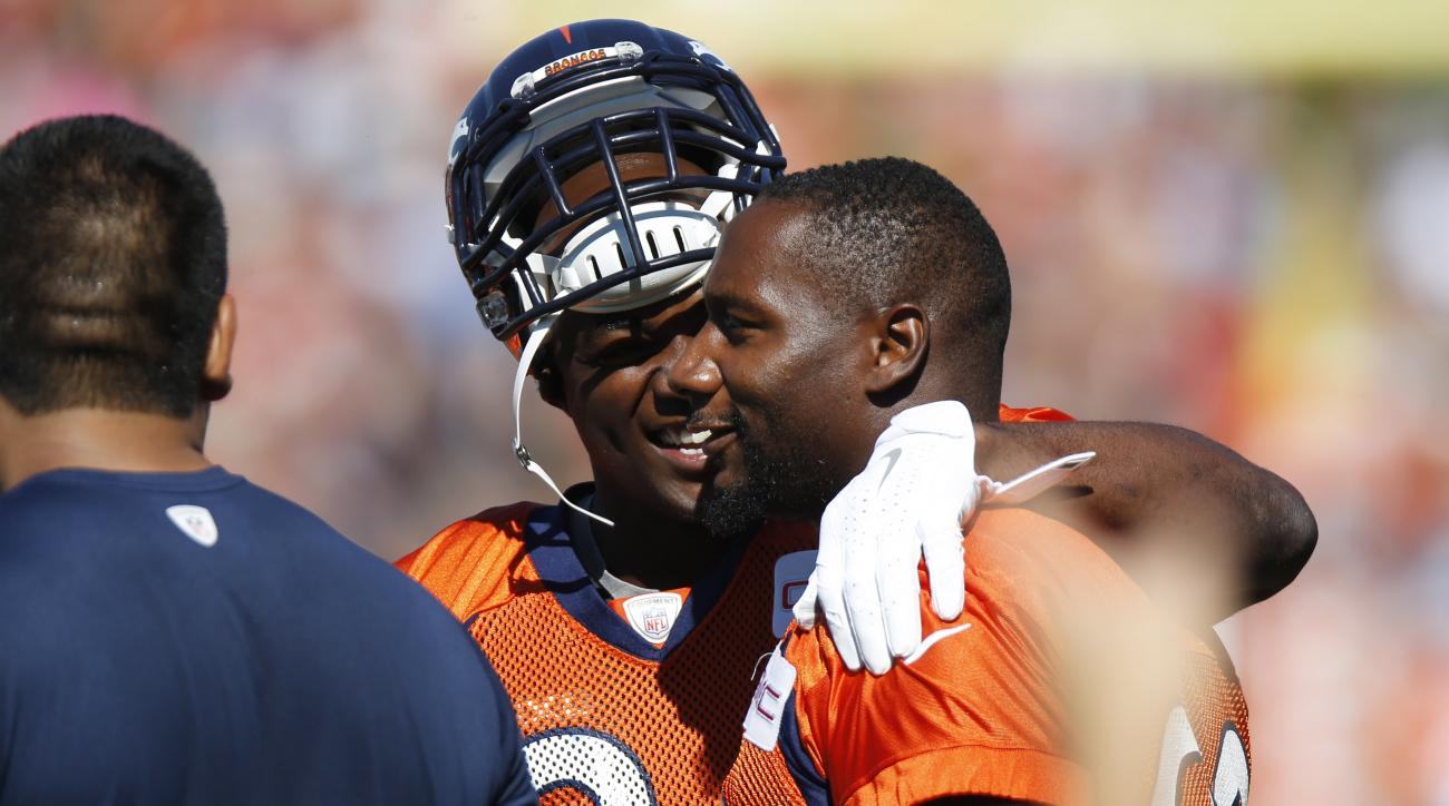 Denver Broncos defensive end Antonio Smith, front, is welcomed to the field by fellow lineman DeMarcus Ware at the team's NFL football training camp Friday, July 31, 2015, in Englewood, Colo. (AP Photo/David Zalubowski)