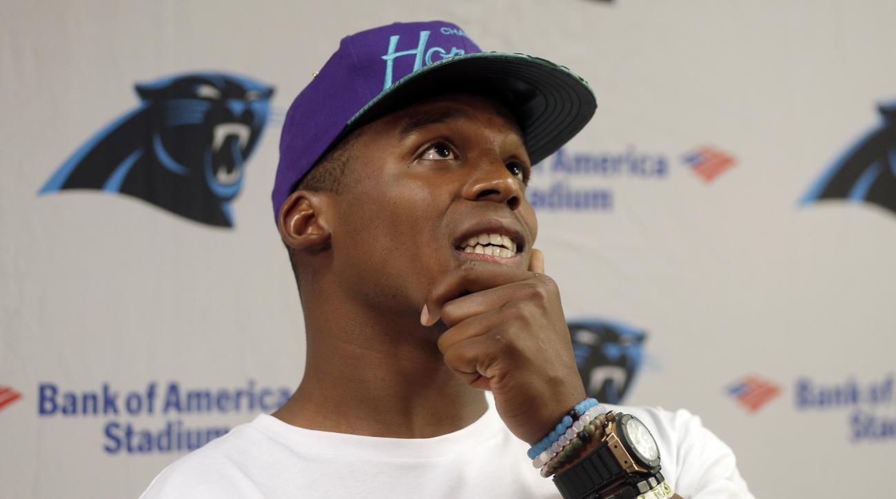 "Carolina Panthers' Cam Newton ponders a question during a news conference at the NFL football team's training camp in Spartanburg, S.C., Friday, July 31, 2015. The ""Fall Risk"" bracelet on his arm is a reminder of his hospital stay after an auto accident l"