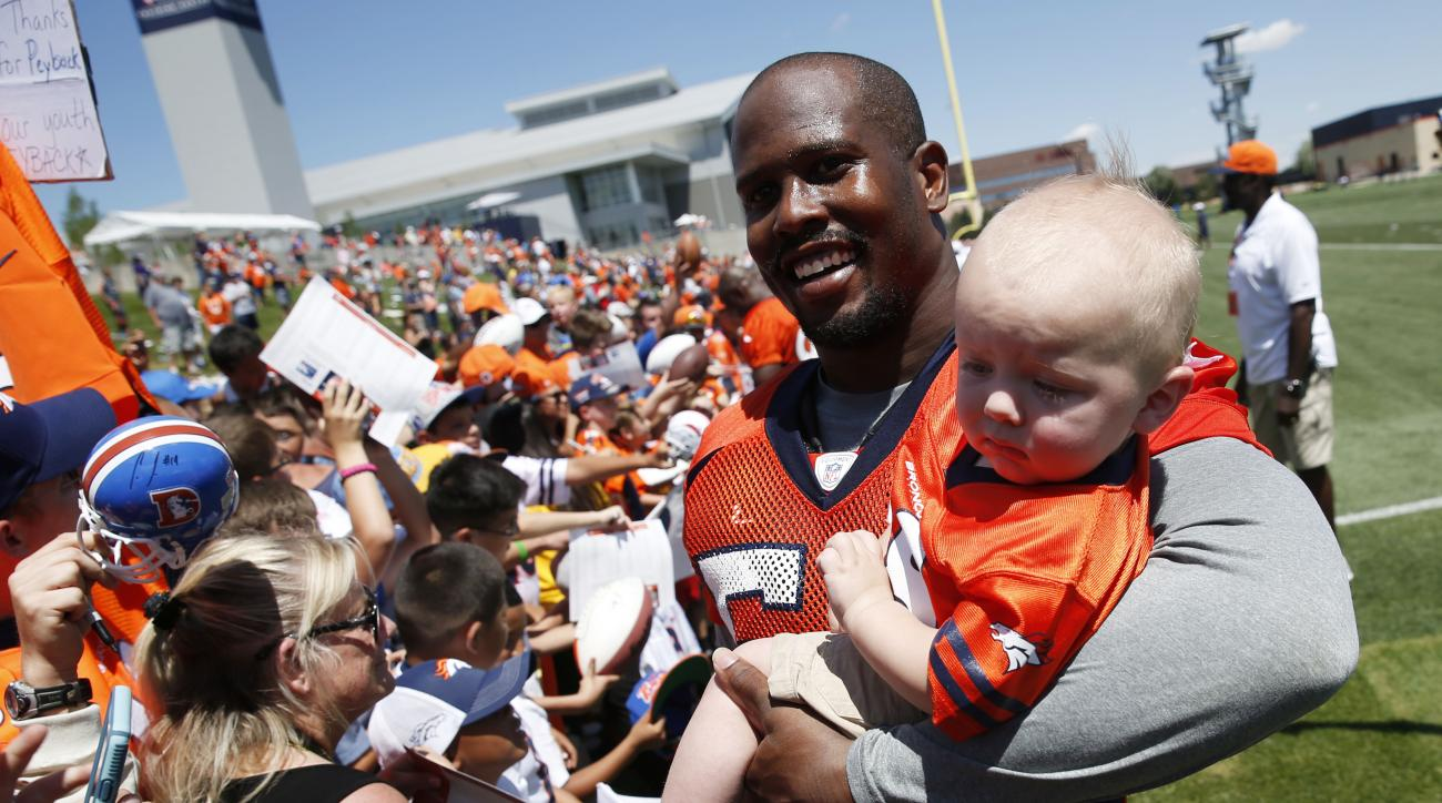 Denver Broncos outside linebacker Von Miller holds an unidentified child while greeting fans after the opening session at the team's NFL football training camp Friday, July 31, 2015, in Englewood, Colo. (AP Photo/David Zalubowski)