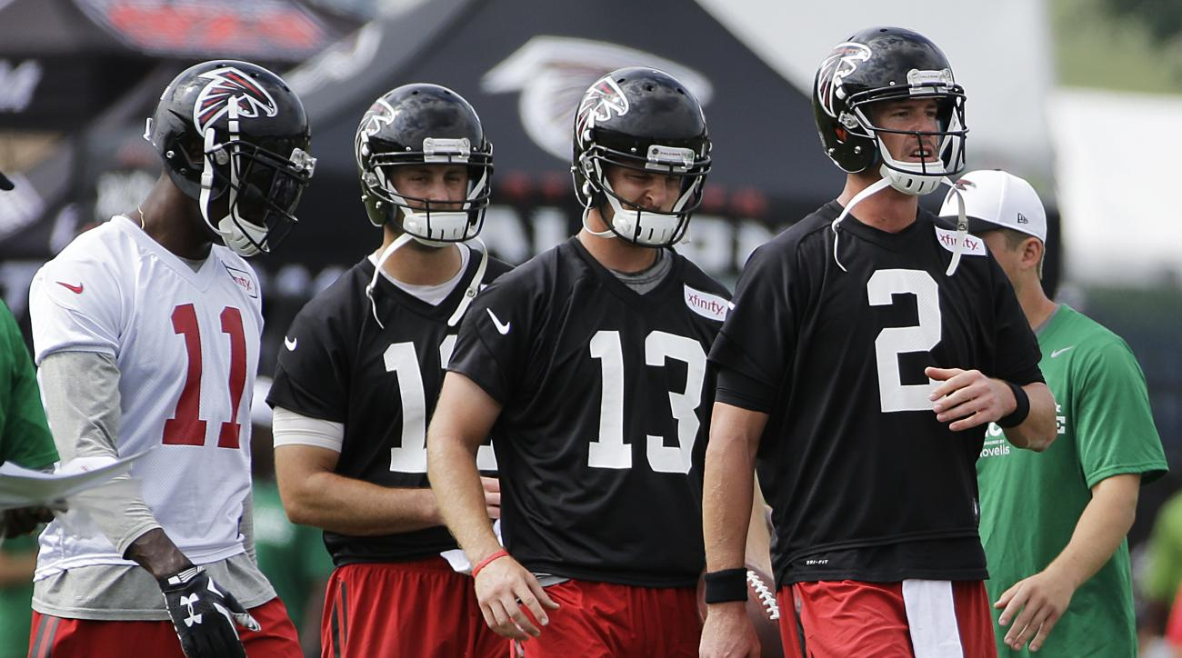 Atlanta Falcons quarterback Matt Ryan, right, leads a drill with fellow quarterbacks T.J. Yates (13) and Sean Renfree, rear, as wide receiver Julio Jones, left, walks on the field during NFL football training camp Saturday, Aug. 1, 2015, in Flowery Branch