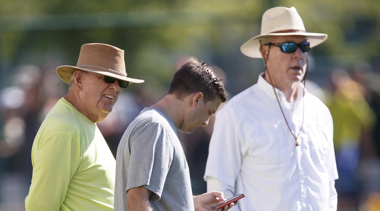 Former Green Bay Packers General Manager Ron Wolf, left, talks with his son Eliot Wolf, the team's director of player personnel, as current General Manager Ted Thompson, right, looks on during NFL football training camp, Saturday, Aug. 1 , 2015, in Green
