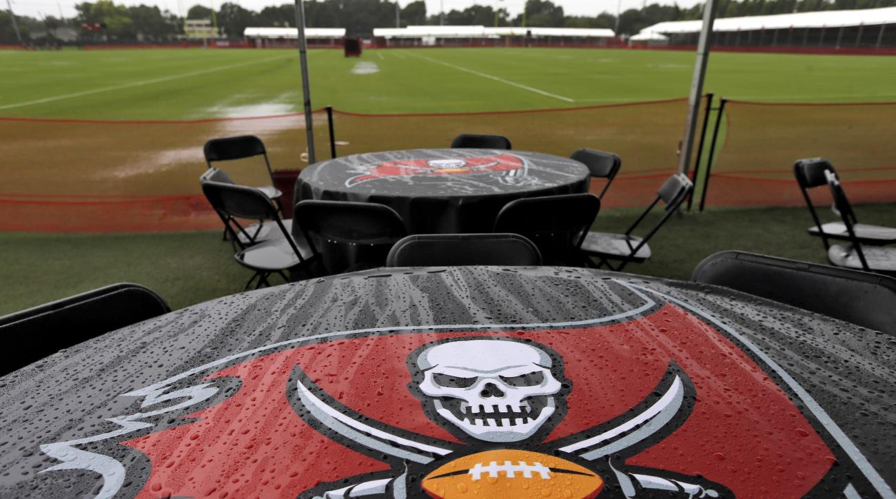 Raindrops cling to tablecloths near flooded practice fields at Tampa Bay Buccaneers training camp Saturday, Aug. 1, 2015, in Tampa, Fla. The first day of camp was canceled due to inclement weather. (AP Photo/Chris O'Meara)