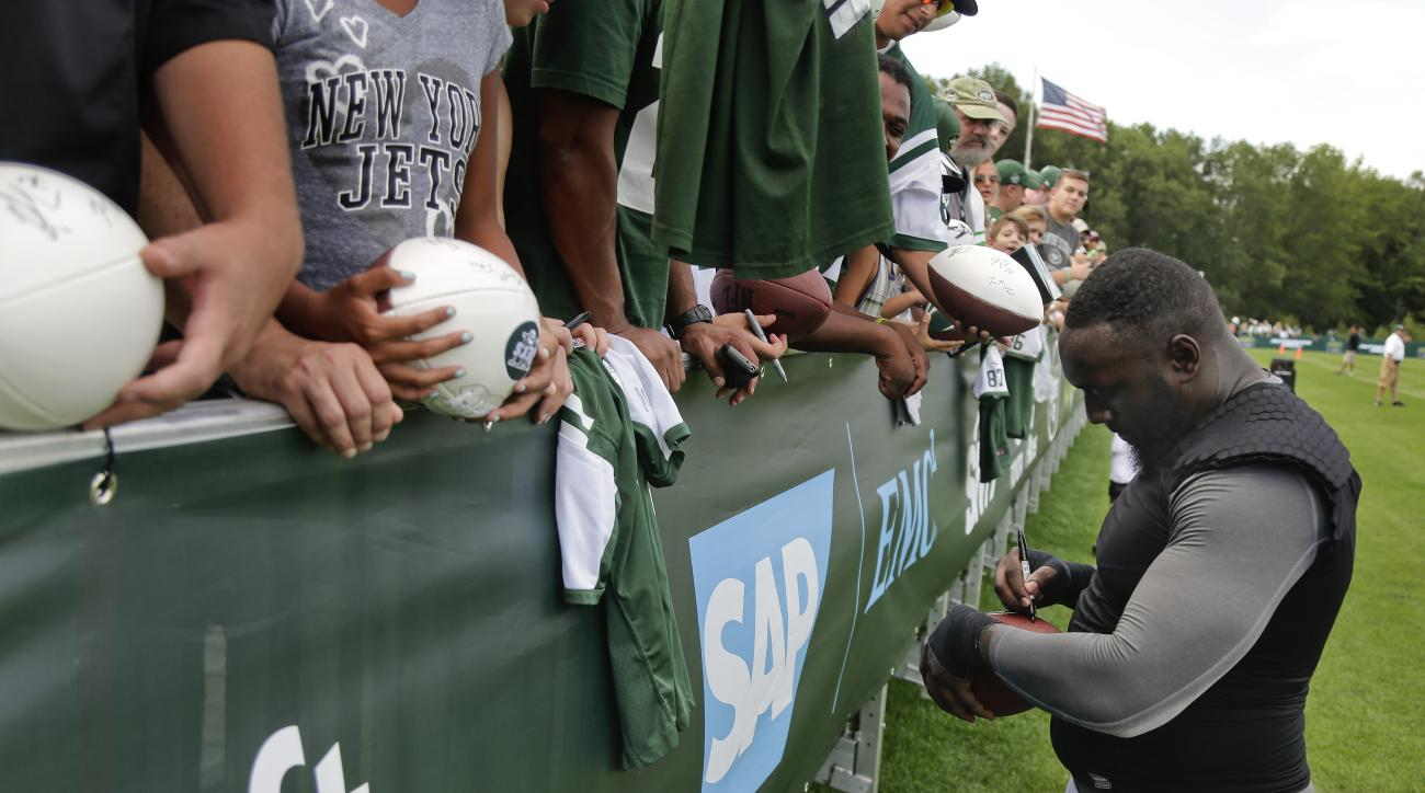 New York Jets defensive end Muhammad Wilkerson signs autographs for fans after practice at the team's NFL football training camp, Saturday, Aug. 1, 2015, in Florham Park, N.J.. (AP Photo/Julie Jacobson)