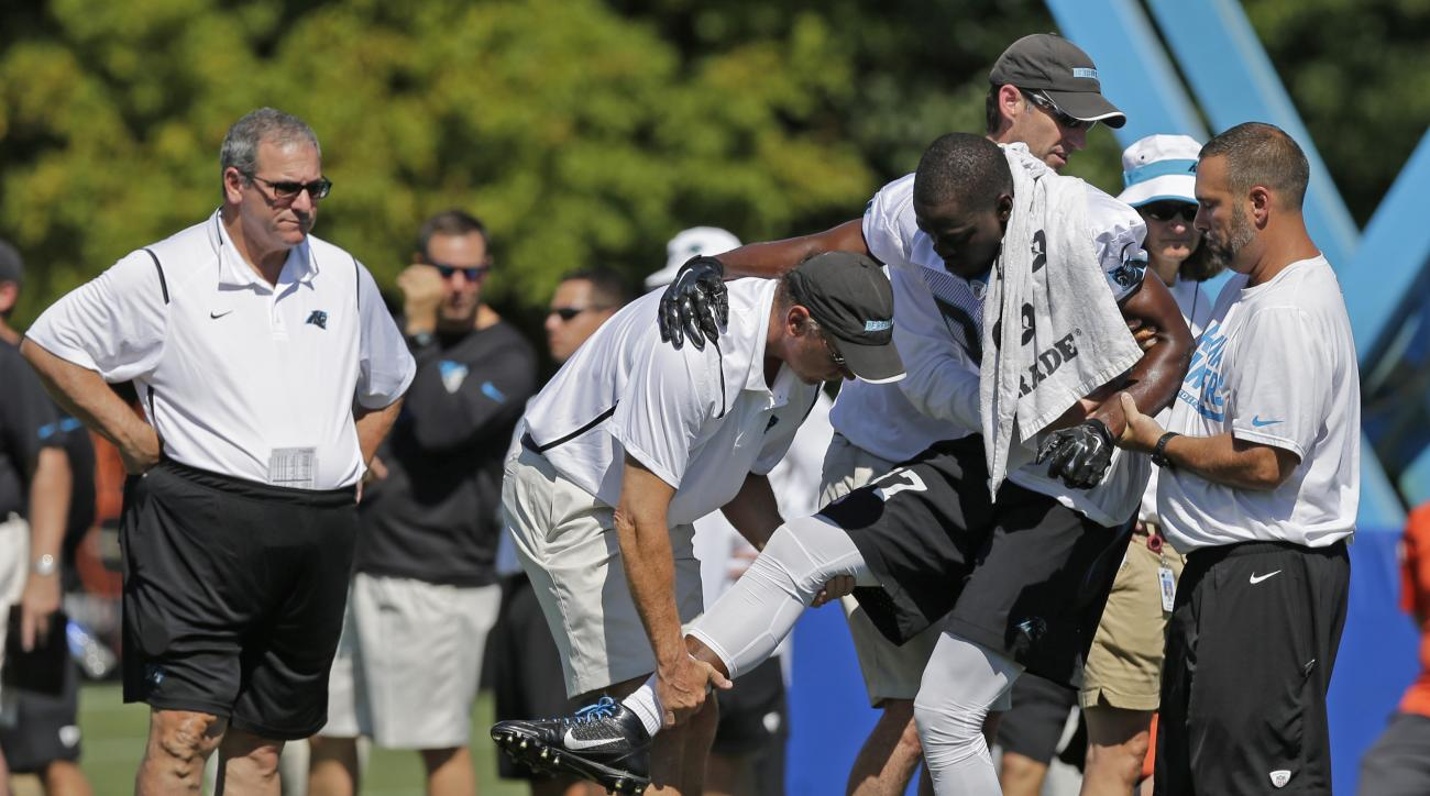 Trainers assist Carolina Panthers' Stephen Hill (87) after being injured during the NFL football team's training camp in Spartanburg, S.C., Saturday, Aug. 1, 2015. Carolina Panthers general manager Dave Gettleman, left, looks on. (AP Photo/Chuck Burton)