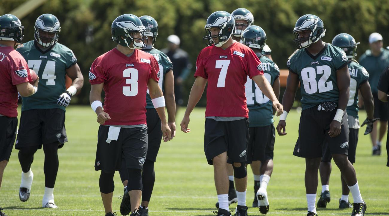 Philadelphia Eagles quarterback Sam Bradford (7) talks with quarterback Mark Sanchez (3) as they warm up during practice at NFL football training camp, Sunday, Aug. 2, 2015, in Philadelphia. (AP Photo/Chris Szagola)