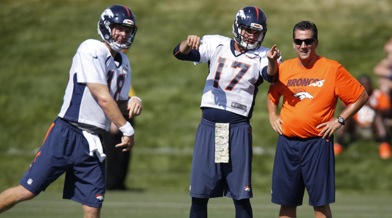 Denver Broncos quarterback Peyton Manning, left, throws while backup quarterback Brock Osweiler confers with quarterbacks coach Greg Knapp during drills at the team's NFL football training camp Sunday, Aug. 2, 2015, in Englewood, Colo. (AP Photo/David Zal