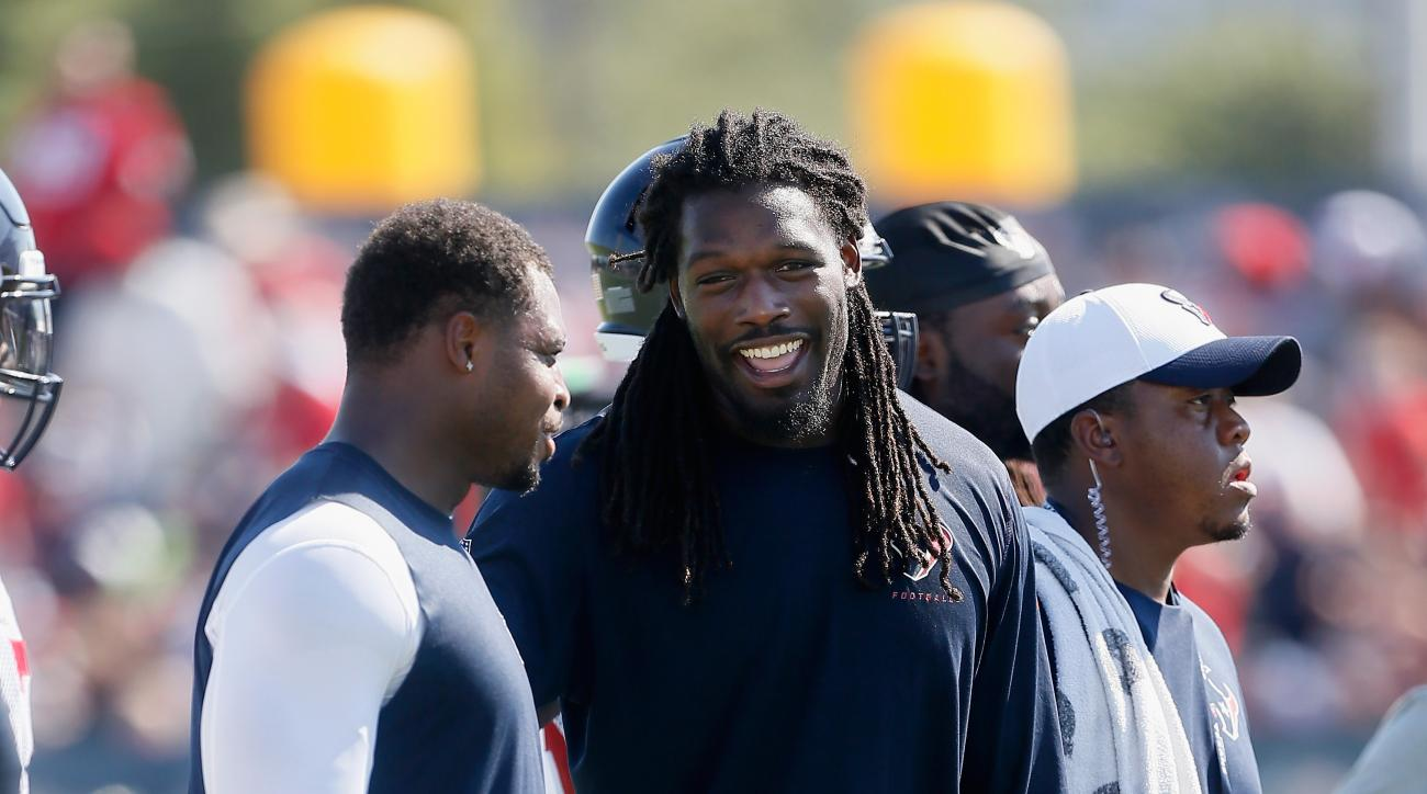 Houston Texans linebacker Jadeveon Clowney, center, talks during NFL football training camp at the Methodist Training Center on Sunday, Aug. 2, 2015, in Houston. (AP Photo/Bob Levey)