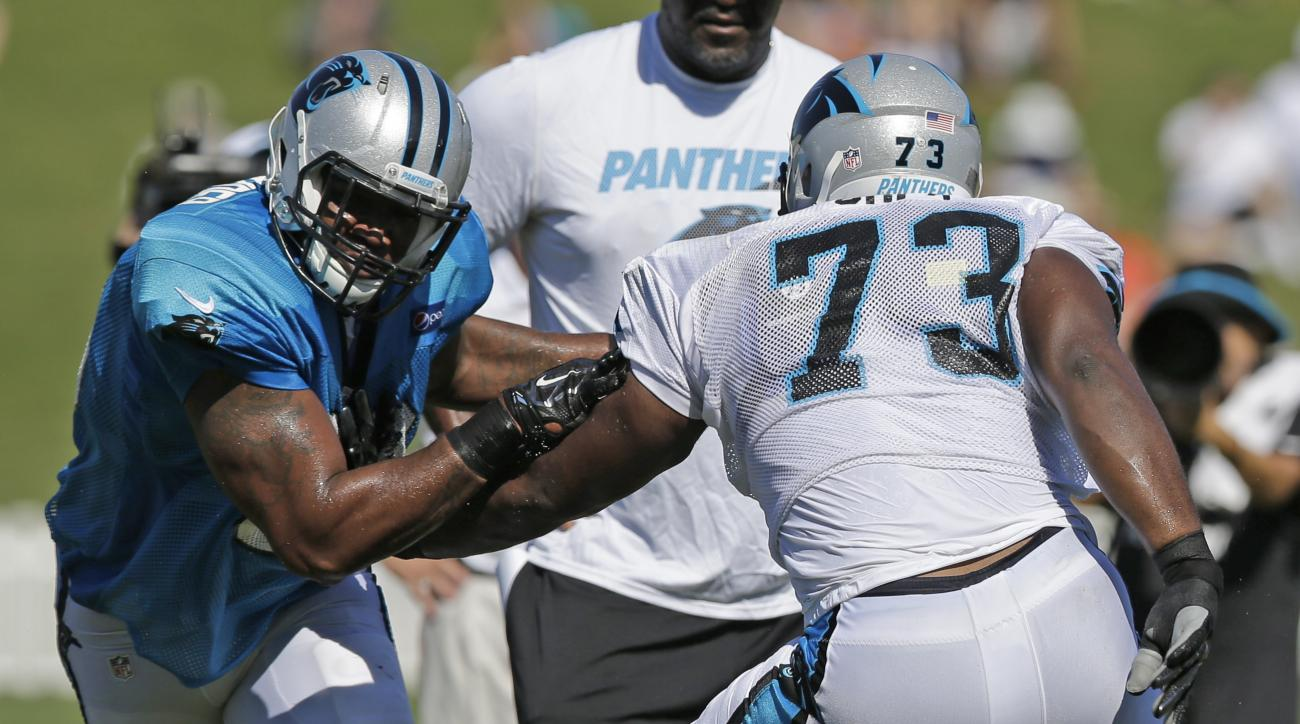 Carolina Panthers' Michael Oher, right, tries to block Frank Alexander, left, during the NFL football team's training camp in Spartanburg, S.C., Sunday, Aug. 2, 2015. (AP Photo/Chuck Burton)