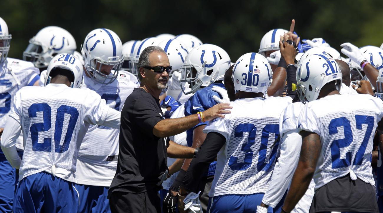 Indianapolis Colts head coach Chuck Pagano greets players as they huddled as the team opened training camp in Anderson, Ind., Sunday, Aug. 2, 2015.  (AP Photo/Michael Conroy)