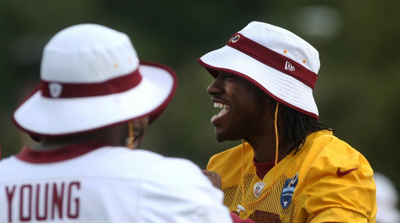 Washington Redskins quarterback Robert Griffin III, right, laughs with Washington Redskins fullback Darrel Young during the team's NFL football training camp in Richmond, Va., Monday, Aug. 3, 2015.   (AP Photo/Jason Hirschfeld)