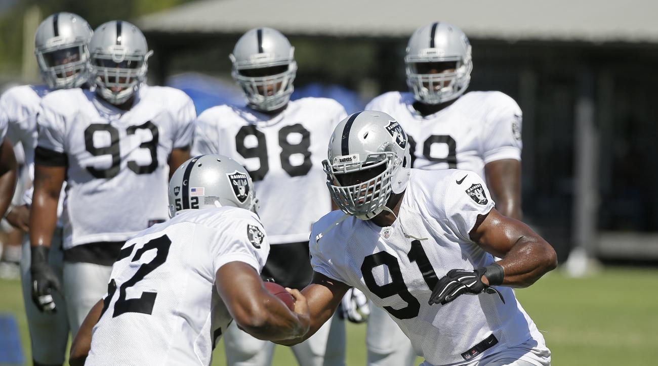 Oakland Raiders outside linebacker Khalil Mack, left, carries the ball in a drill against defensive end Justin Tuck (91) during their NFL football training camp Monday, Aug. 3, 2015, in Napa, Calif. In the background is defensive tackle Ricky Lumpkin (93)