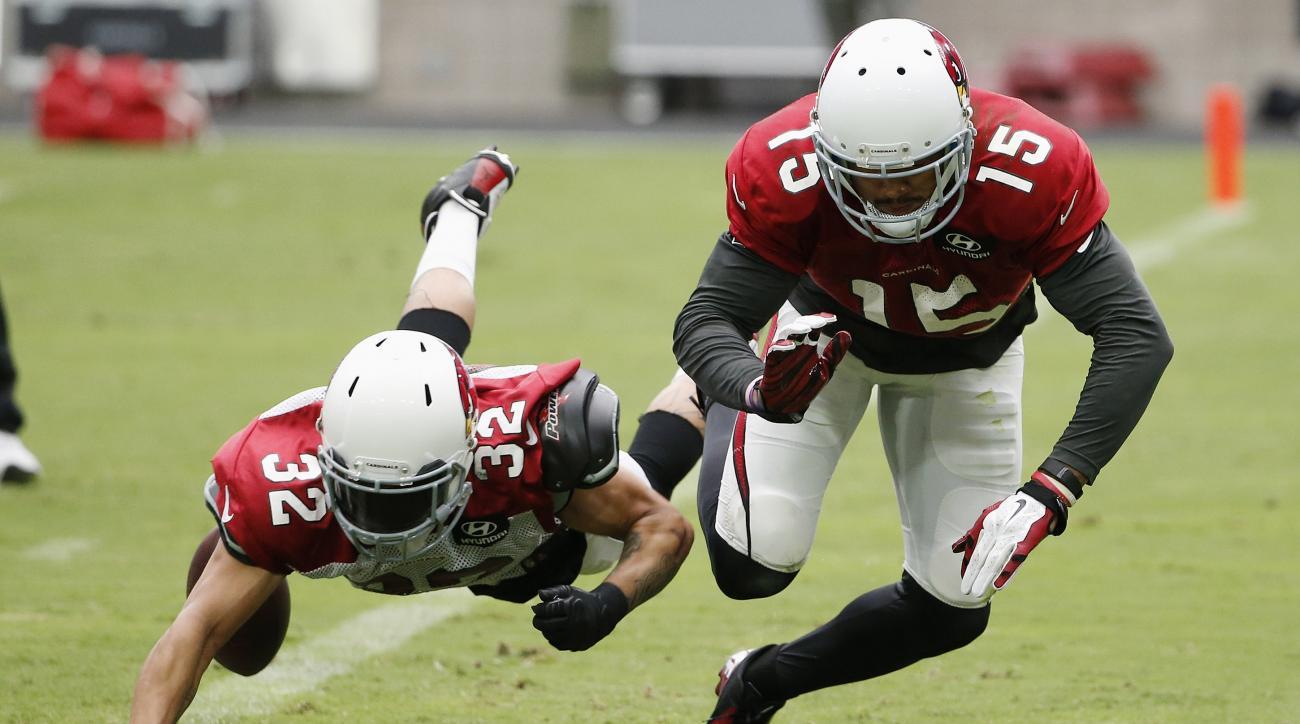 Arizona Cardinals' Tyrann Mathieu (32) tips the ball away from Cardinals' Michael Floyd (15) during an NFL football training camp practice, Monday, Aug. 3, 2015, in Glendale, Ariz. (AP Photo/Ross D. Franklin)