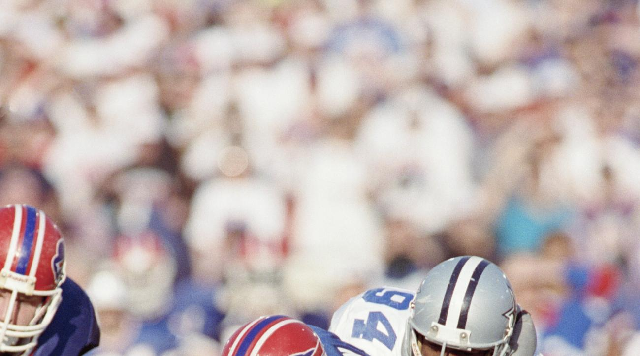 FILE - In this Jan. 31, 1999, file photo, Buffalo Bills quarterback Jim Kelly has the ball striped by Dallas Cowboys Charles Haley during the first quarter of Super Bowl XXVII in Pasadena, Calif.  The play was nulified for a  holding call and Buffalo was