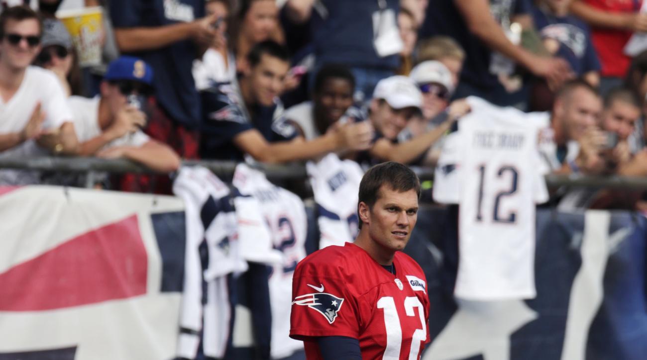 New England Patriots quarterback Tom Brady walks onto the field at Gillette Stadium prior to an NFL football training camp, Wednesday, Aug. 5, 2015, in Foxborough, Mass. (AP Photo/Charles Krupa)