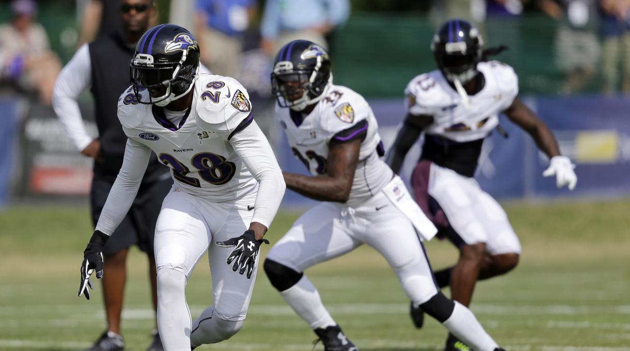 Baltimore Ravens defensive back Brynden Trawick, left, runs a drill during NFL football training camp, Thursday, Aug. 6, 2015, in Owings Mills, Md. (AP Photo/Patrick Semansky)