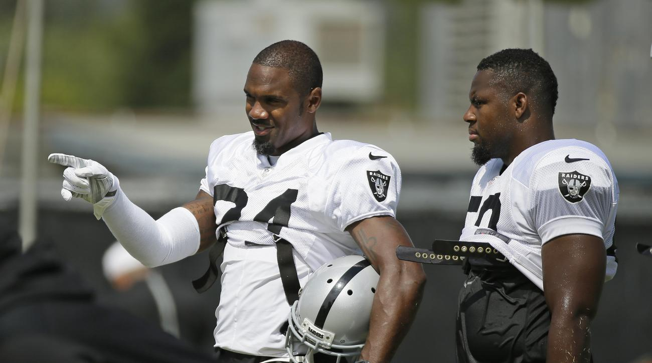 Oakland Raiders free safety Charles Woodson, left, talks with linebacker Curtis Lofton, right, during their football training camp Thursday, Aug. 6, 2015, in Napa, Calif. (AP Photo/Eric Risberg)