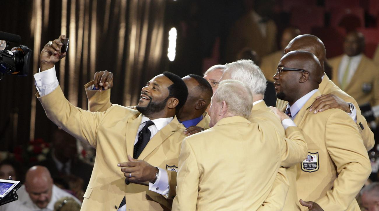 Jerome Bettis takes a selfie with fellow members of the Pro Football Hall of Fame Class of 2015, Thursday, Aug. 6, 2015, in Canton, Ohio. (Bob Rossiter/The Repository via AP)