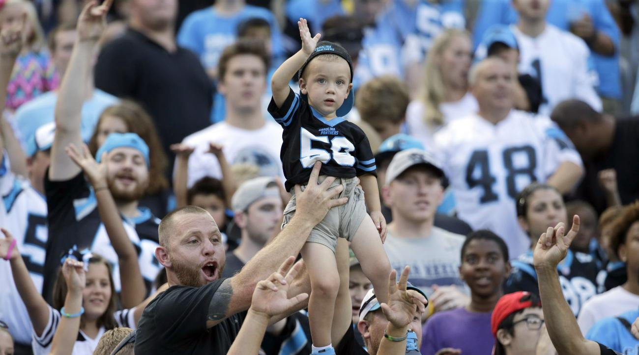 A man holds a young boy up as they cheer the Carolina Panthers players who take the field during the annual Fan Fest during the NFL football team's training camp in Charlotte, N.C., Friday, Aug. 7, 2015. (AP Photo/Chuck Burton)