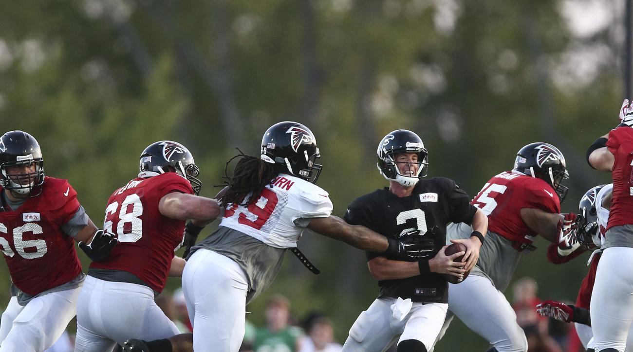 "Atlanta Falcons defensive end Adrian Clayborn (99) gets a hand on quarterback Matt Ryan during the the team's annual ""Friday Night Lights"" NFL football practice Friday, Aug. 7, 2015, in Buford, Ga. (AP Photo/John Bazemore)"