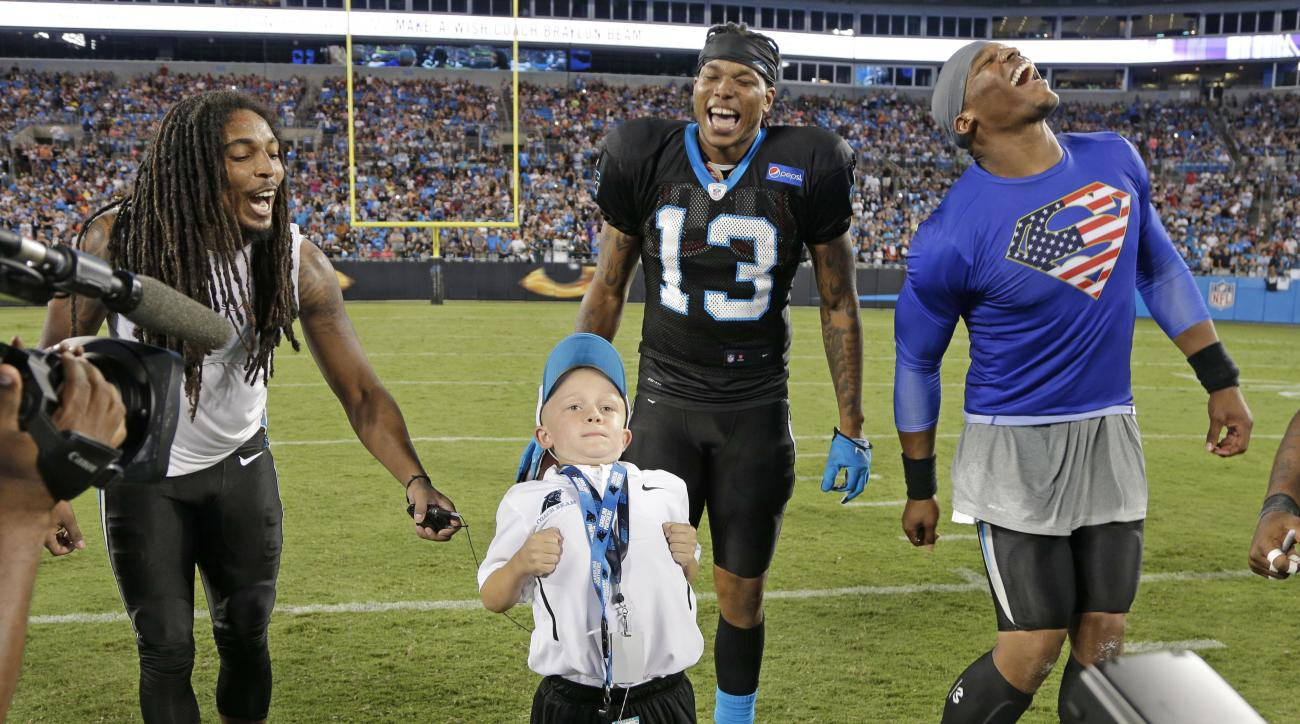 Carolina Panthers players, from right, Cam Newton, Kelvin Benjamin, and Tre Boston, laugh as Braylon Beam performs Newton's Superman celebration during the annual Fan Fest at the NFL football team's training camp in Charlotte, N.C., Friday, Aug. 7, 2015.