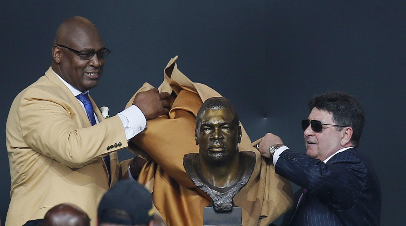 Former NFL player Charles Haley, left, unveils his bust with his presenter, former San Francisco 49ers owner Edward DeBartolo Jr., during an induction ceremony at the Pro Football Hall of Fame, Saturday, Aug. 8, 2015, in Canton, Ohio. (AP Photo/Tom E. Pus