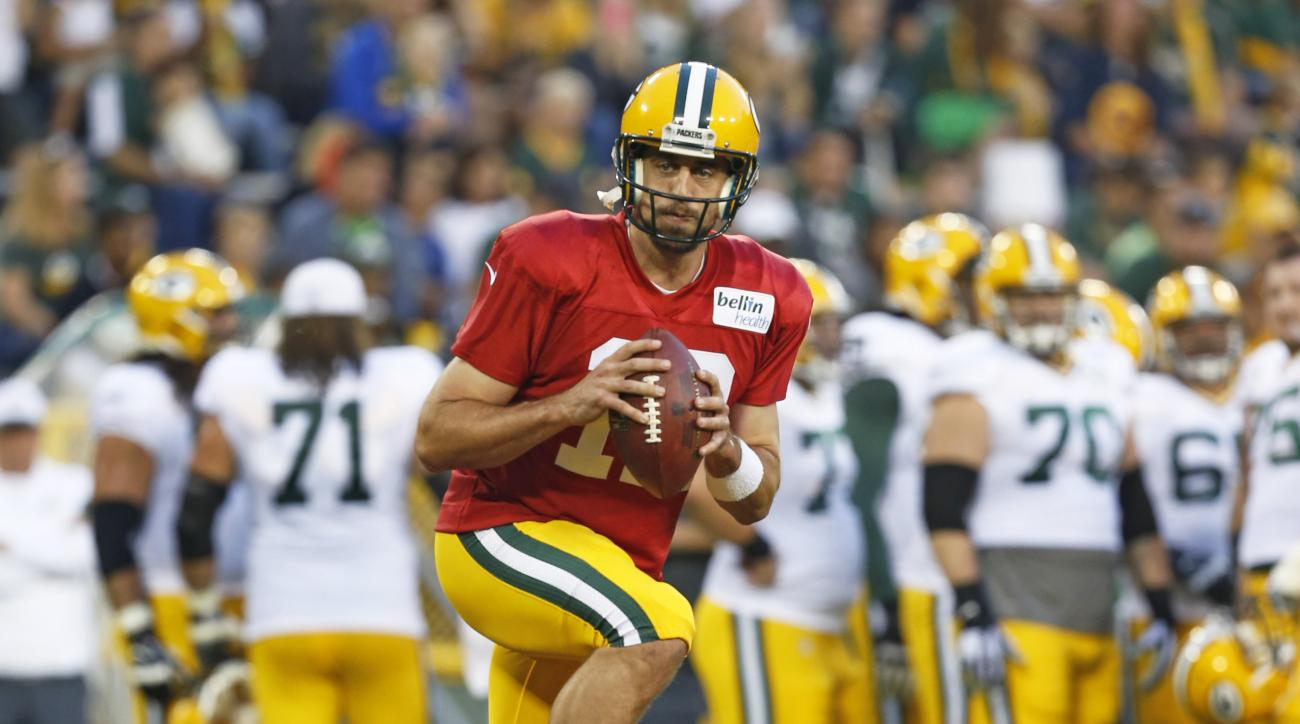 Green Bay Packers quarterback Aaron Rodgers runs through a drill during the NFL football team's Family Fun Night as part of training camp, Saturday, Aug. 8, 2015, in Green Bay, Wis. (AP Photo/Mike Roemer)