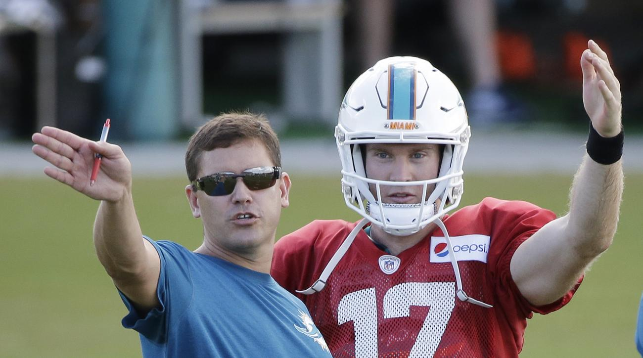 Miami Dolphins quarterback Ryan Tannehill (17) talks with offensive coordinator Bill Lazor during an NFL football training camp practice, Tuesday, Aug. 11, 2015 in Davie, Fla. (AP Photo/Wilfredo Lee)