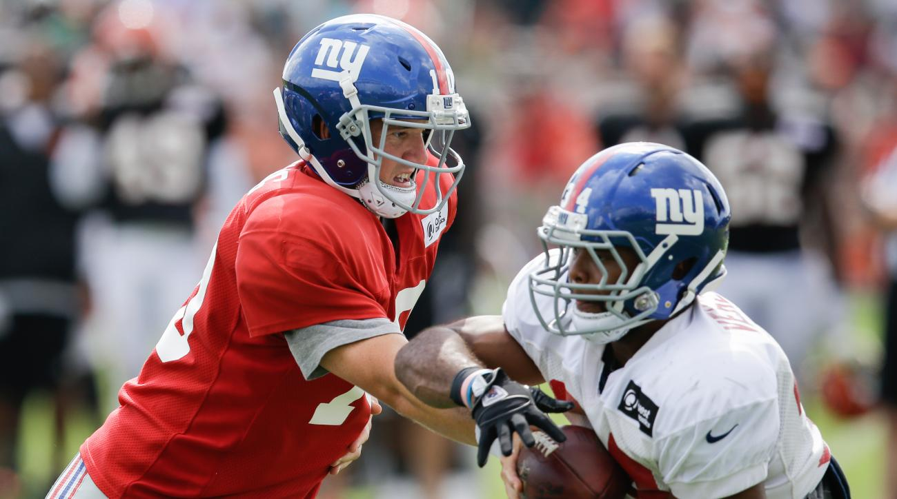New York Giants quarterback Eli Manning, left, hands the ball off to running back Shane Vareen during NFL football training camp, Tuesday, Aug. 11, 2015, in Cincinnati. (AP Photo/John Minchillo)