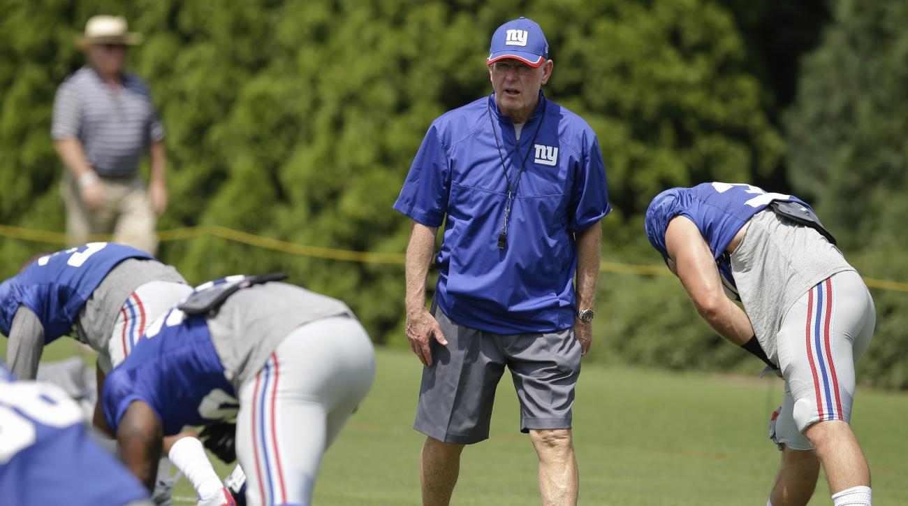 New York Giants coach Tom Coughlin walks the field as his players warm up during NFL football training camp, Tuesday, Aug. 11, 2015, in Cincinnati. (AP Photo/John Minchillo)
