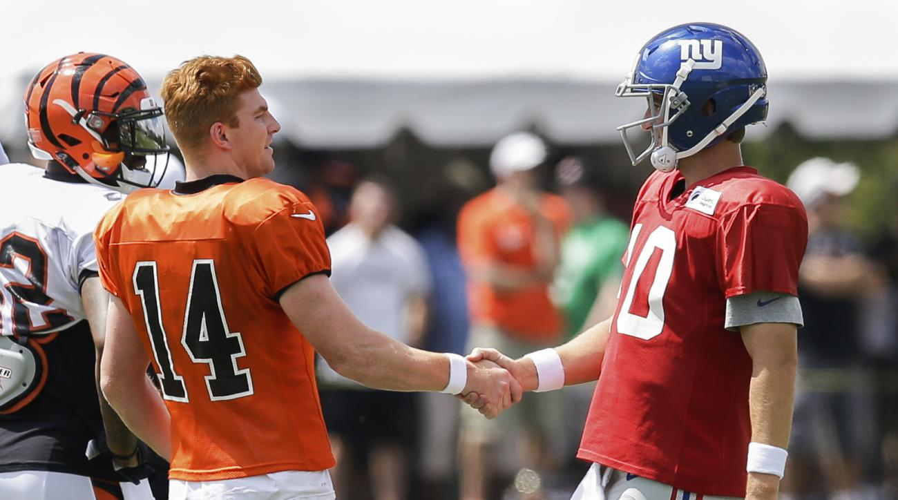 Cincinnati Bengals quarterback Andy Dalton, left, shakes hands with New York Giants quarterback Eli Manning during NFL football training camp, Tuesday, Aug. 11, 2015, in Cincinnati. (AP Photo/John Minchillo)