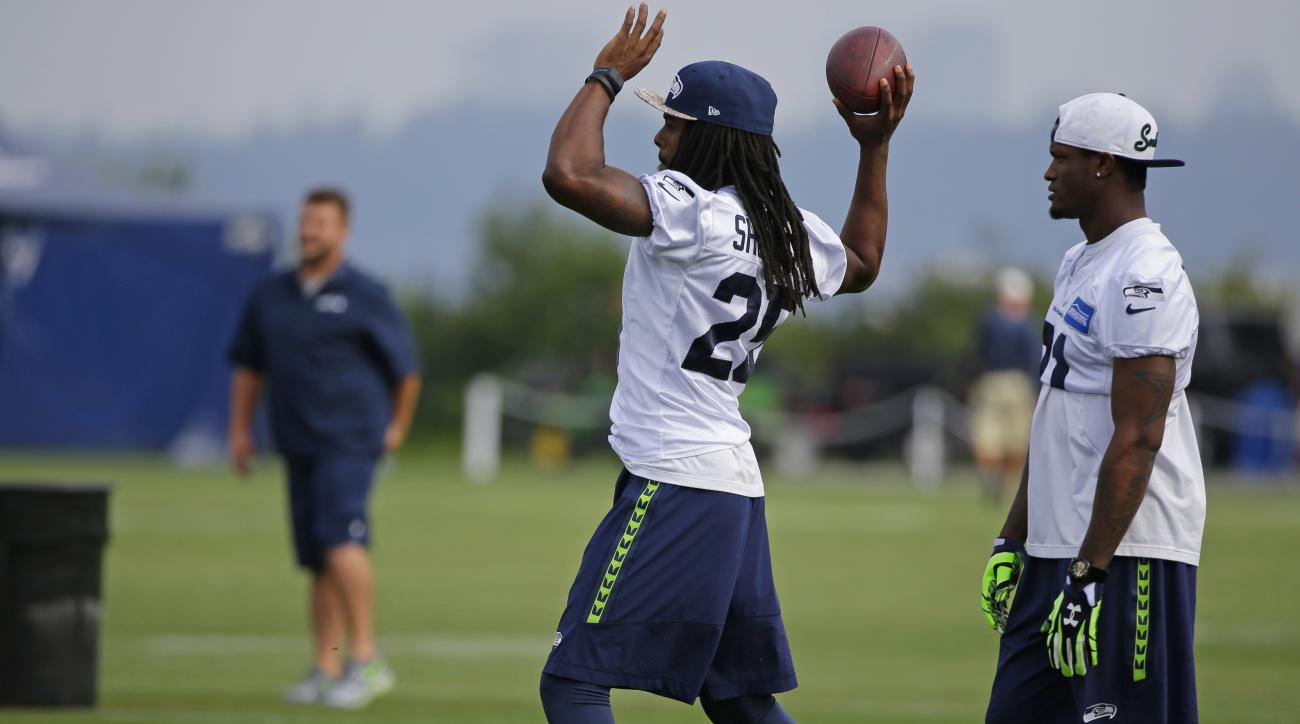 Seattle Seahawks cornerbacks Richard Sherman, left, and Will Blackmon, right, stand on the sidelines during NFL football training camp, Thursday, Aug. 13, 2015, in Renton, Wash. The Seahawks host the Denver Broncos in a preseason game in Seattle on Friday