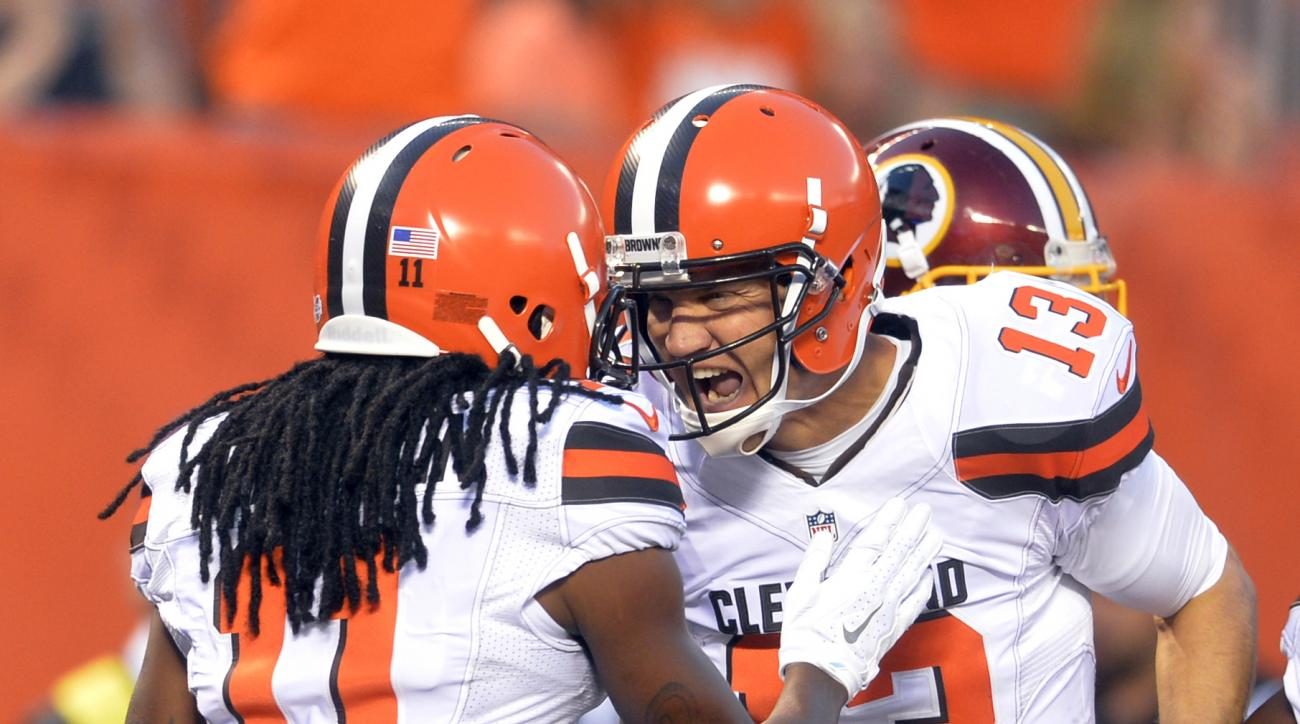 Cleveland Browns quarterback Josh McCown (13) celebrates with Travis Benjamin (11) after a 2-yard touchdown by Benjamin during the first quarter of an NFL preseason football game, Thursday, Aug. 13, 2015, in Cleveland. (AP Photo/David Richard)