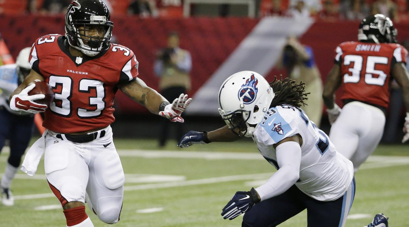 Atlanta Falcons running back Terron Ward (33) runs against Tennessee Titans strong safety Daimion Stafford (39) during the first half of an NFL football preseason game , Friday, Aug. 14, 2015, in Atlanta. (AP Photo/David Goldman)