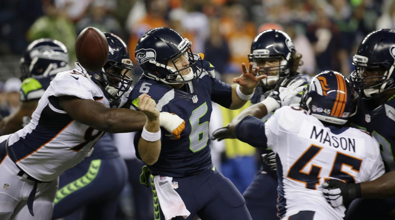 Denver Broncos defensive end Kenny Anunike, left, sacks Seattle Seahawks quarterback R.J. Archer (6) and causes him to fumble the ball out of bounds during the second half of a preseason NFL football game, Friday, Aug. 14, 2015, in Seattle. (AP Photo/Elai