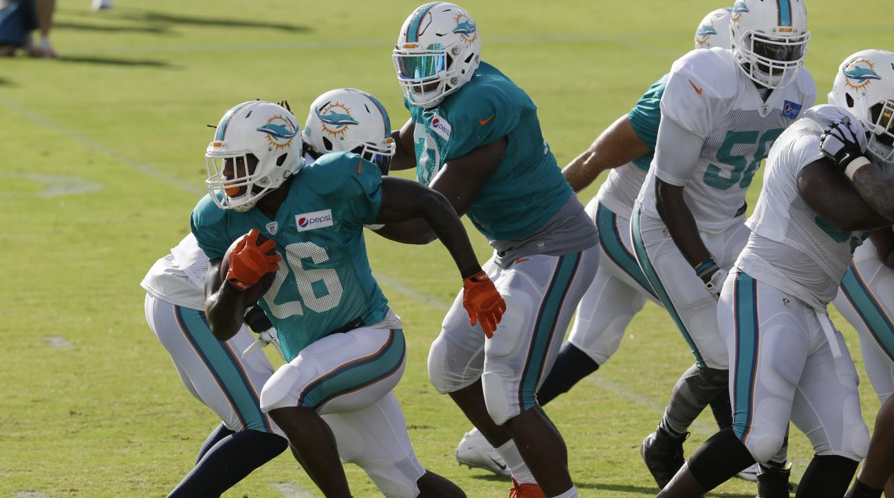 Miami Dolphins running back Lamar Miller (26) runs with the football during an NFL training camp practice, Sunday, Aug. 16, 2015, in Davie, Fla. (AP Photo/Lynne Sladky)