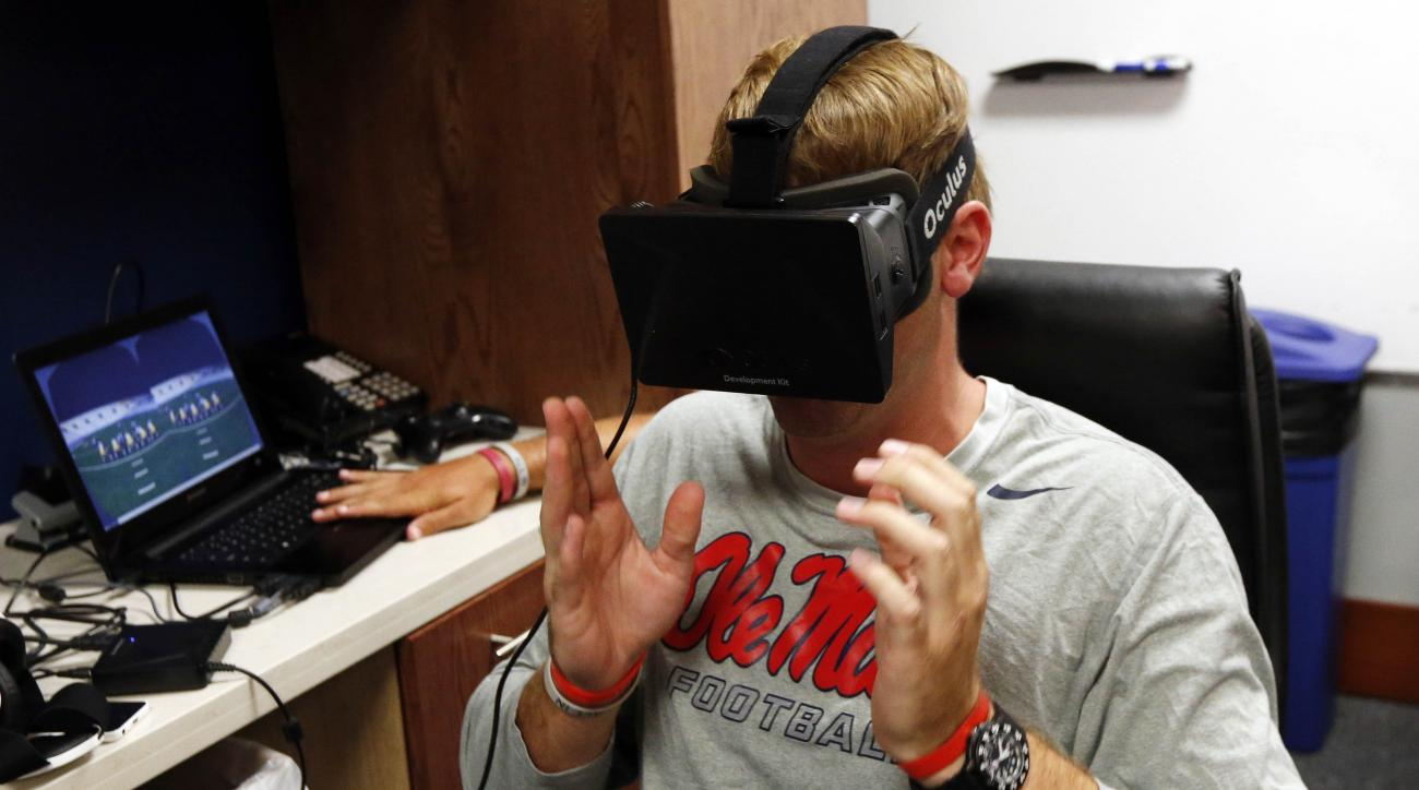 In this July 27, 2015 photo, Mississippi quarterback Ryan Buchanan uses a virtual reality headset to make football play decisions at the Manning Center in Oxford, Miss. Ole Miss is one of a growing number of football programs in the NCAA and NFL dabbling