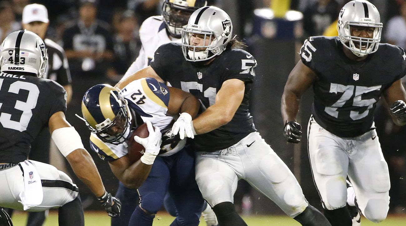 In this Aug. 14, 2015,  photo, Oakland Raiders inside linebacker Ben Heeney (51) tackles St. Louis Rams running back Trey Watts (42) during the first half of an NFL preseason football game in Oakland, Calif. Linebacker Heeney's exhibition debut for Oaklan