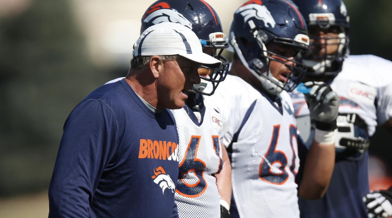 Denver Broncos offensive line coach Clancy Barone, front, directs his squad during the morning session at the team's NFL football training camp Tuesday, Aug. 18, 2015, in Englewood, Colo. (AP Photo/David Zalubowski)