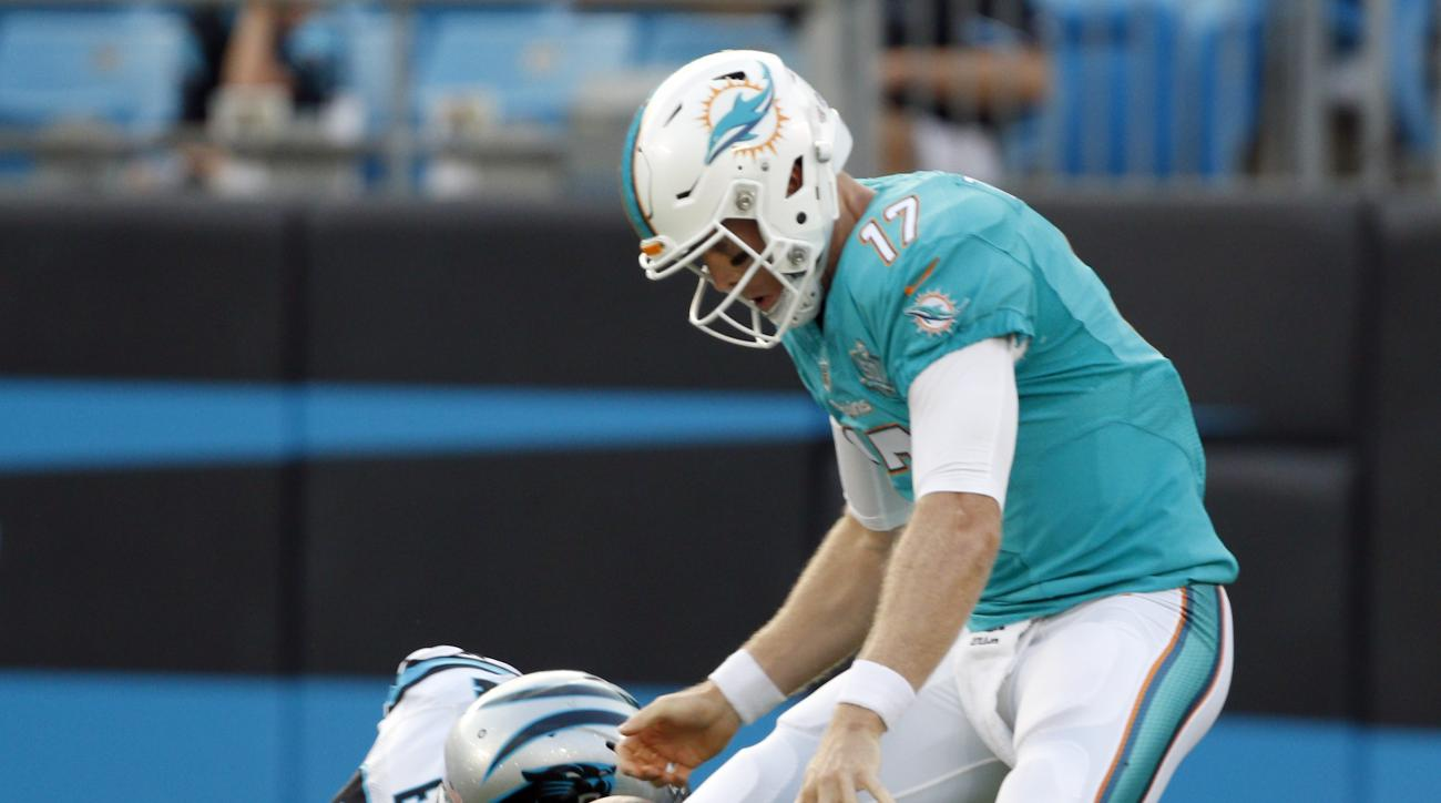 Miami Dolphins' Ryan Tannehill (17) fumbles the ball after being hit by Carolina Panthers' Kony Ealy (94) during the first half of an NFL preseason football game in Charlotte, N.C., Saturday, Aug. 22, 2015. Tannehill recovered the ball. (AP Photo/Bob Leve