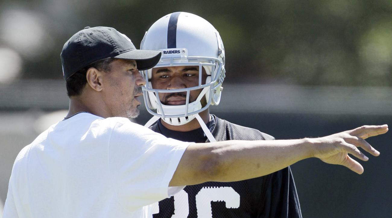 FILE - In this July 29, 2011, file photo, Oakland Raiders cornerback Stanford Routt, right, listens to assistant defensive backs coach Rod Woodson, left, during their NFL football training camp in Napa, Calif. The Oakland Raiders brought in 10 men with 10