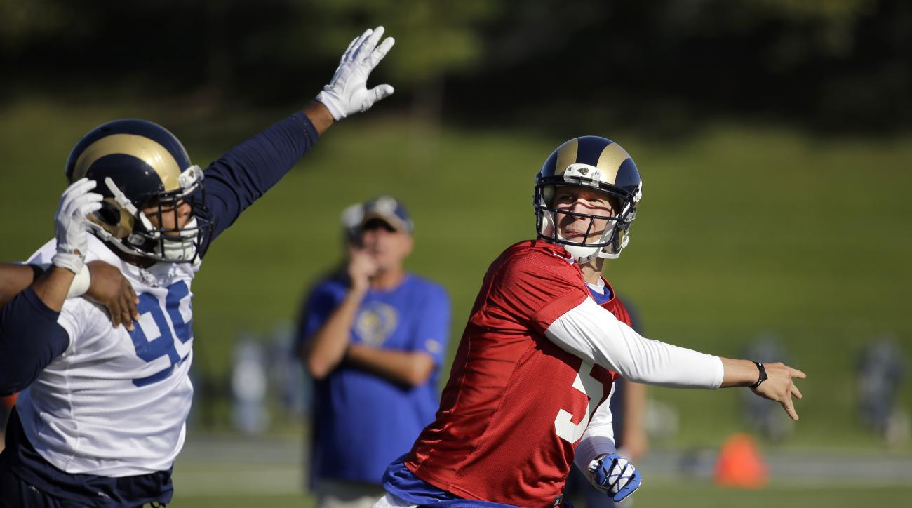 St. Louis Rams quarterback Nick Foles, right, follows through on a pass as defensive tackle Aaron Donald defends during training camp at the NFL football team's practice facility Tuesday, Aug. 25, 2015, in St. Louis. (AP Photo/Jeff Roberson)