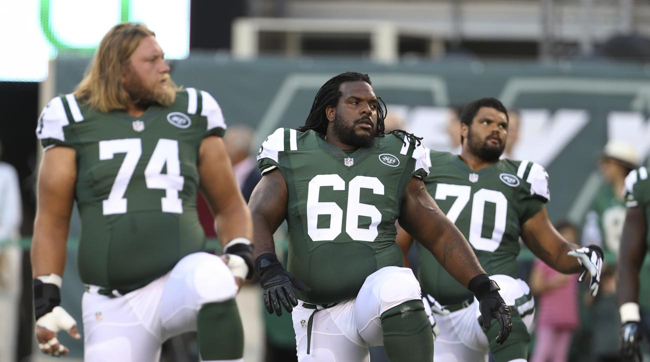 FILE - In this Friday, Aug. 21, 2015, file photo, New York Jets guard Willie Colon (66) stretches with teammates Nick Mangold (74), Dakota Dozier (70) and Jarvis Harrison (64) before an NFL preseason football game against the Atlanta Falcons in New York.