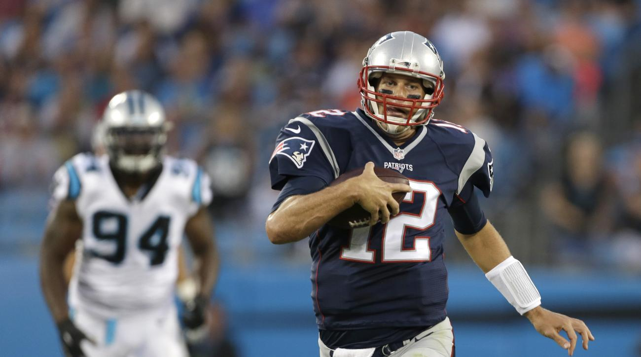 New England Patriots' Tom Brady (12) scrambles as Carolina Panthers' Kony Ealy (94) pursues during the first half of a preseason NFL football game in Charlotte, N.C., Friday, Aug. 28, 2015. (AP Photo/Bob Leverone)